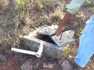 Miembros de la cooperativa me muestran partes del suministro de agua saboteado - ahora secos después de válvulas se han robado y tubos cortado