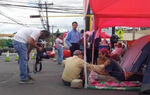 Fuera del cordón policial, más de los huelgistas, ahora sin comida varios días, se mezclan con los medios de comunicación y otros manifestantes